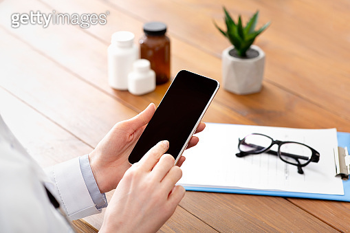 Mobile app and support patients online remotely. Lady middle aged doctor typing on smartphone