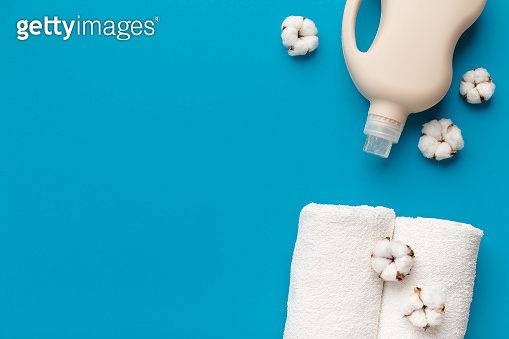 Bio plastic Bottle of detergent or softener and a pile of clean towels