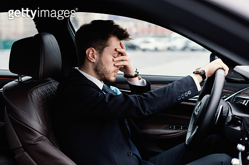 Sad businessman driving alone in his new car
