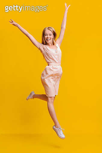 Carefree teen girl jumping in the air with raised arms