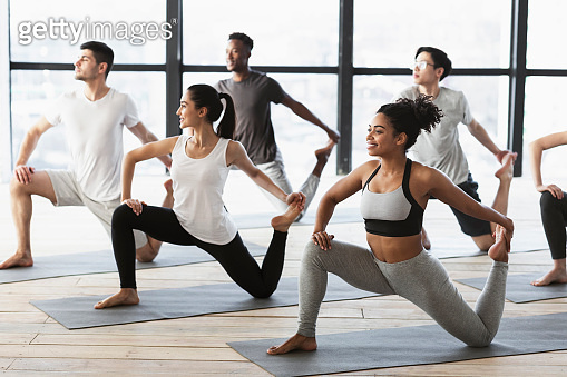 Yoga practice. Group of interracial young people doing Mermaid pose