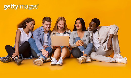 International group of teenagers looking at laptop screen