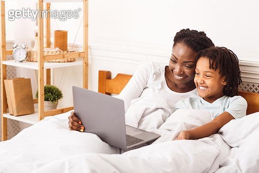 African american woman and girl watching cartoons on laptop