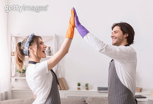 Young Spouses Giving High Five To Each Other After Cleaning Flat Together