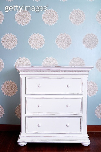 White night table against floral pattern wall