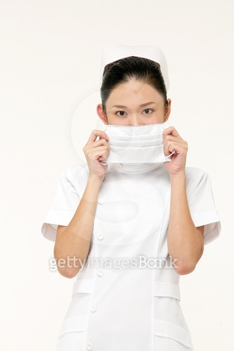 Portrait of a nurse holding a surgical mask