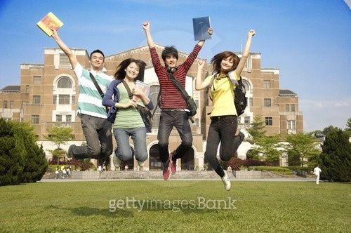 University students jumping together in a lawn
