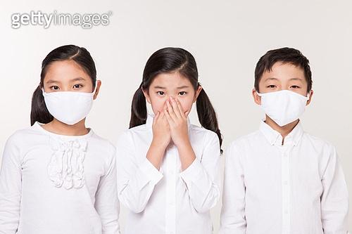 양옆의 소녀 소년이 마스크를 착용하고 중심에 있는 소녀가 손으로 코와 입을 가린다