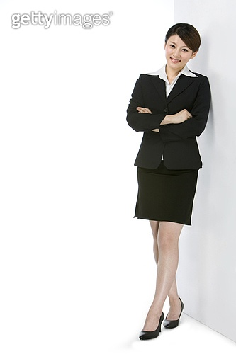 Smiling young businesswoman standing against wall