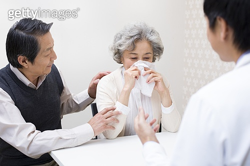 Senior man consoling wife in hospital