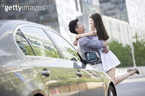 Young couple embracing next to their car