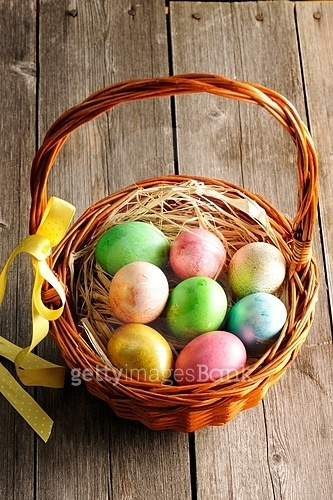 Colored easter eggs in basket on wooden table