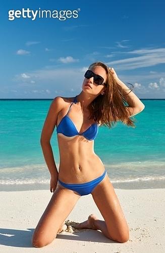 Woman in bikini at tropical beach sitting on her knees