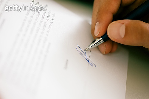 Man (only hand to be seen) signing a contract or another document (fake signature)