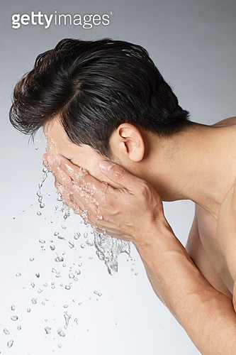 Young men wash face