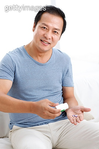 Middle-aged man holding a capsule