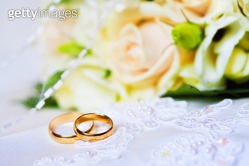 wedding rings with bouquet from roses