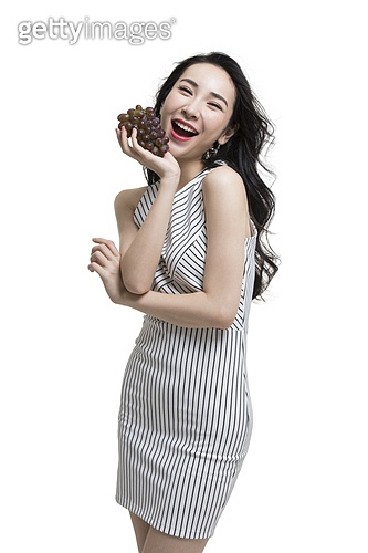 Fashionable young woman holding grapes