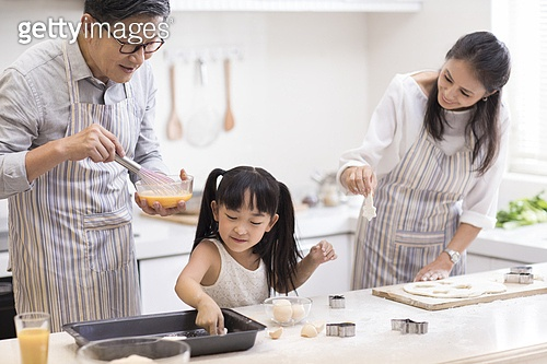 Happy little girl and grandparents baking cookies in kitchen