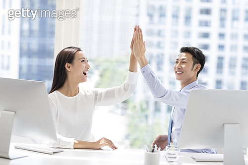 Confident business people high fiving in office