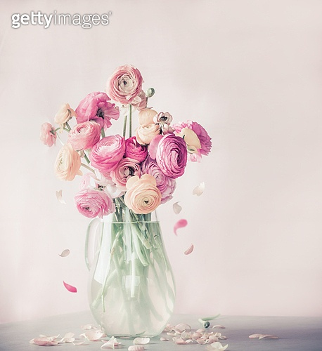 Pastel color ranunculus flowers bouquet with falling petals in glass vase on table, front view