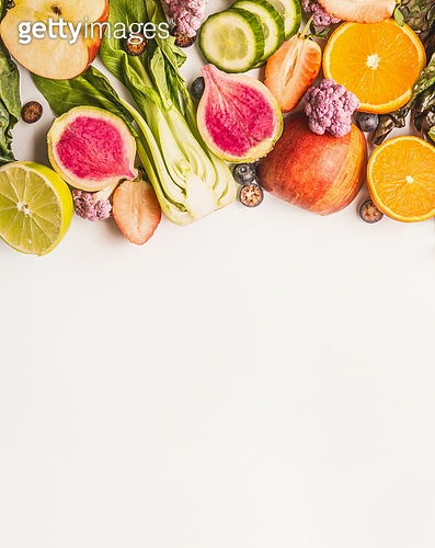 Variety of fresh colorful fruits, citrus and vegetables on white background, top view, border. Healthy food and clean eating ingredients concept