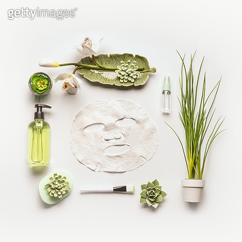 Modern facial skin care setting . Herbal cosmetic concept.  Flat lay Sheet mask with green cosmetic products, accessories, plants and orchid flowers on white desktop background, top view, copy space