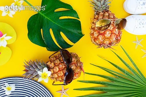 Summer top view flat lay pattern with pair pineapples on bright yellow background. Summer flat lay scenery