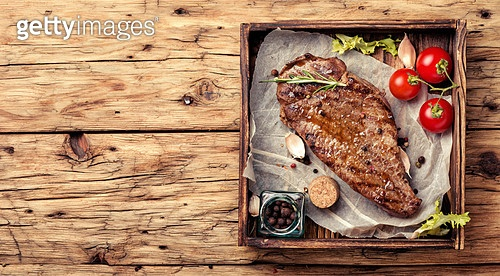 Grilled ribeye beef steak, herbs and spices.Delicious festive steak. Beef steak on a wooden background