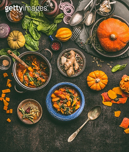 Overhead view of colorful vegetarian pumpkin stew in cooking pot and bowls with spinach and ingredients on dark rustic kitchen table background, top view. Autumn seasonal rustic country food