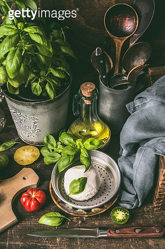 Plate with mozzarella or burrata , oil and basil on rustic kitchen table background with ingredients and cooking tools. Country style food background, still life.