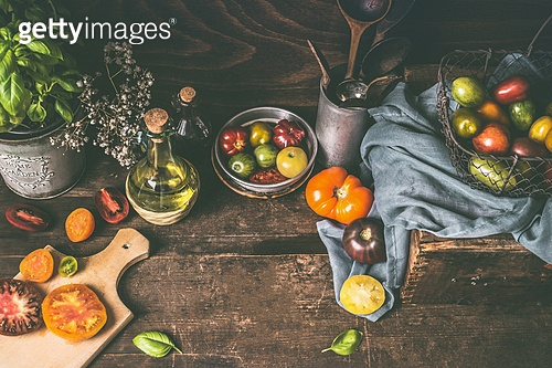 Dark rustic wooden kitchen table with colorful farm tomatoes, ingredients and cooking tools. Country style food background, still life, top view. Place for your design, recipes , text or products
