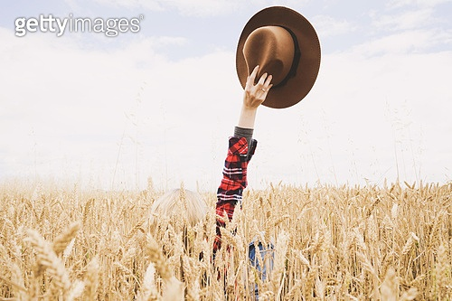 Hand holding a cowboy hat over a field of wheat