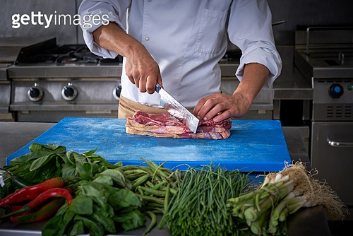 Chef hands cutting meat in restaurant kitchen of stainless steel
