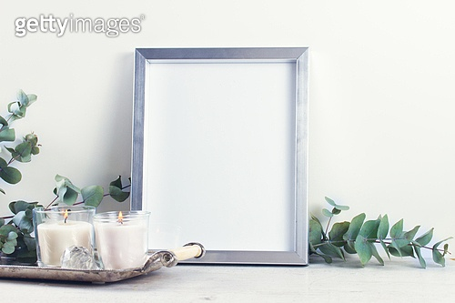 Natural eco home decor. White room interior decor with burning hand-made candle and poster mock up