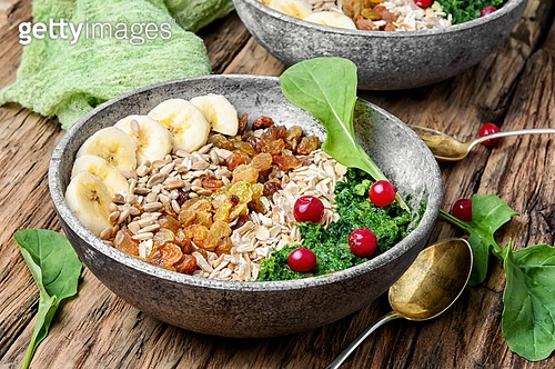 detox breakfast of oatmeal. concept of healthy diet of oatmeal,banana,raisins and spinach