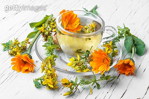 Herbal tea with calendula. Glass cup with herbal medicinal tea from marigold petals