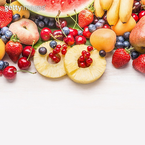 Various healthy fruits on white wooden background, top view, border, copy space