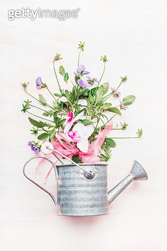 Watering can with bunch of garden flowers on white wooden background, top view