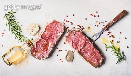 Raw beef Striploin steaks with oil , spices and meat fork on white stone background, top view, flat lay, horizontal