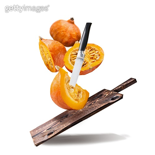 Flying pumpkin with wooden cutting board and knife , isolated on white background. Sliced pumpkin , cooking preparation. Healthy organic seasonal food or diet eating  concept.