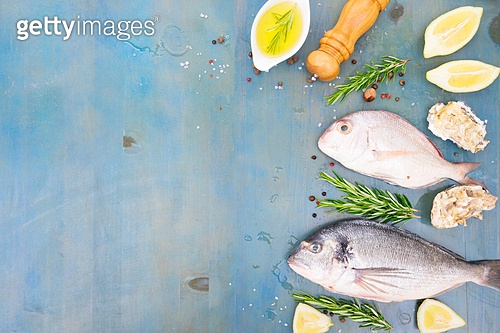 fresh sea fish set - dorada breams with lemon, herbs and spices on blue wooden background. fresh sea fish preparation