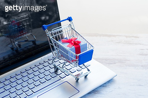 On-line shopping concept - shop cart with giftbox with red bow and laptop keyboard. On-line shopping concept