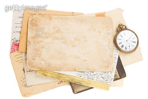 bunch of old photos and papers with antique clock and key isolated on white background