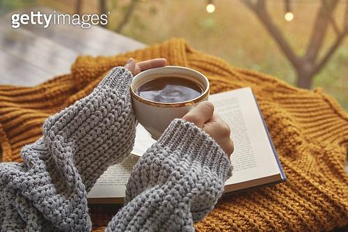 창문 (인조물건), 카페, 계절, 가을, 겨울, 뜨거움 (컨셉), 니트천 (천), 스웨터 (상의), 전구 (전등빛), 테이블, 커피 (뜨거운음료), 커피잔, 책, 사람손 (주요신체부분), 잡기 (물리적활동), 한국인, 동양인 (인종), 성인여자, 아메리카노