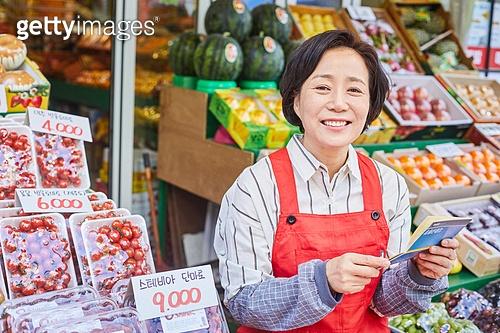 50대 (중년), 여성, 상인 (소매업자), 청과물가게 (가게), 대출, 지원금, 은행통장 (은행서류), 미소