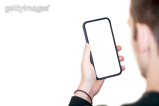 Young adult man looking at the smartphone screen