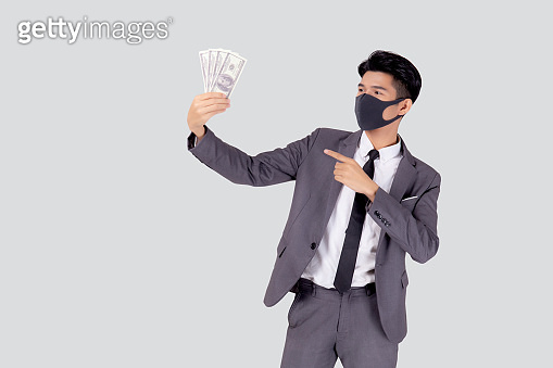 Young asian businessman in  face mask holding money dollar isolated on white background, pandemic and crisis of economic, business man in medical mask and investment during disease covid-19.