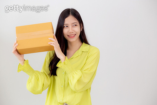Young asian woman smiling and holding cardboard box with surprise at home, happy female carrying parcel box with excited, present and gift, packaging for deliver, online shopping store and service concept.