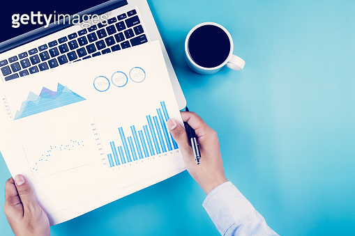 Hand of businessman holding documents report statistic financial with graph and chart and laptop computer and coffee on desk, finance and invest, digital marketing, business and communication concept.